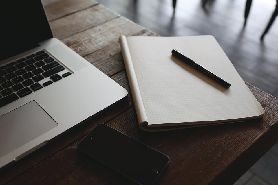 Zdjęcie symboliczne przedstawiająca laptop i notatnik