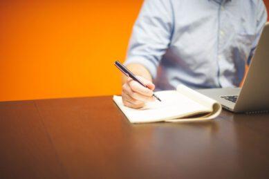 mężczyzna zapisuje dane na kartce